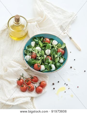 Spring salad with lamb's lettuce, mozarella and cherry-tomatoes in blue ceramic bowl over white back
