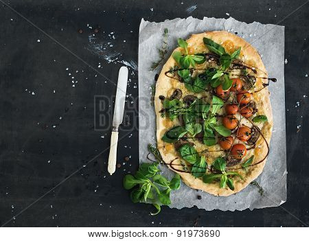 Rustic homemade pizza with fresh lamb's lettuce, mushrooms and cherry-tomatoes over dark grunge back