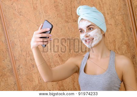 Girl with white clay beauty mask.