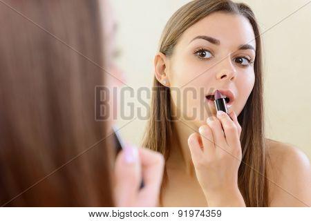 Girl applying lipstick at mirror.