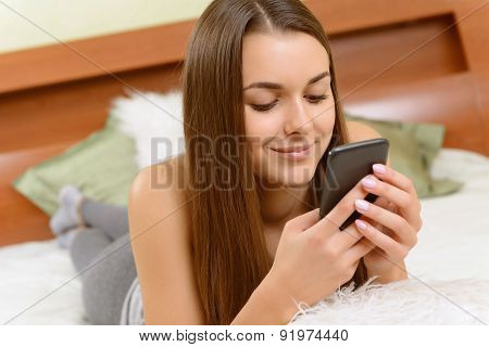 Smiling girl typing messages.