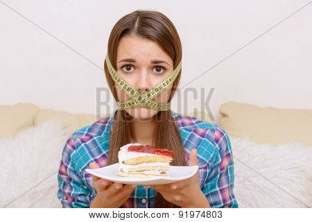 Girl with cake and centimeter band.