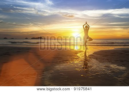 Silhouette of woman standing at yoga pose on the beach during amazing sunset.