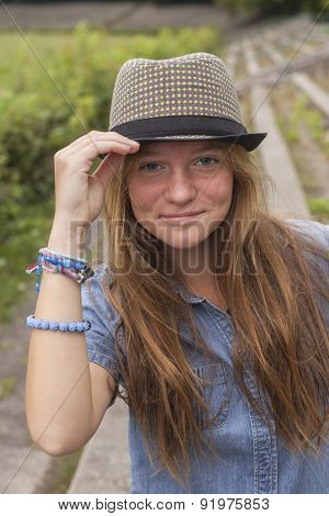 Portrait of a young pretty girl in a hat outdoors, tourism.