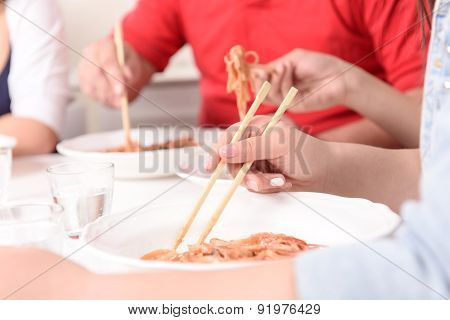 Asians eating with sticks.