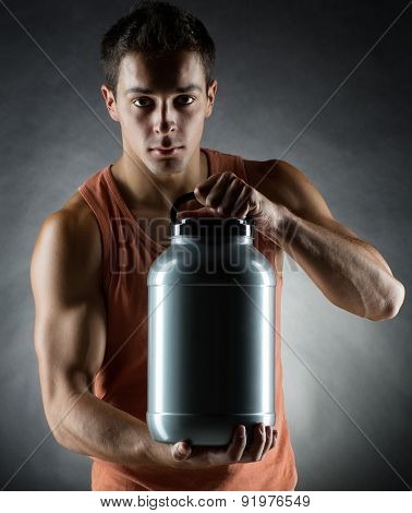 sport, bodybuilding, strength and people concept - young man standing holding jar with protein over gray background