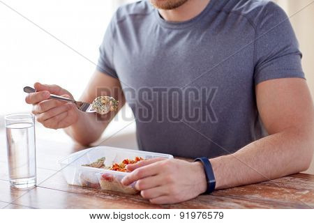 healthy eating, balanced diet, food and people concept - close up of male hands having meat and vegetables for dinner with fork and water glass