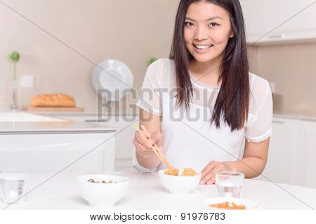 Nice Asian girl eating with sticks