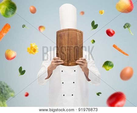 cooking, profession and people concept - male chef cook covering face or hiding behind wooden cutting board over gray background with falling vegetables