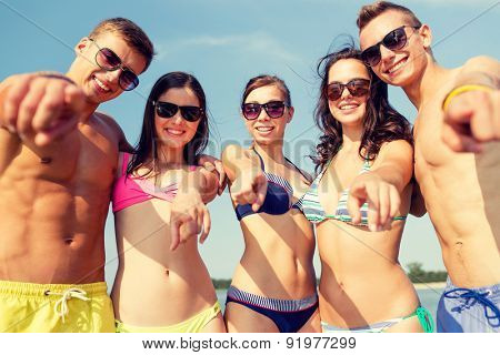 friendship, sea, holidays, gesture and people concept - group of smiling friends wearing swimwear and sunglasses pointing on you on beach