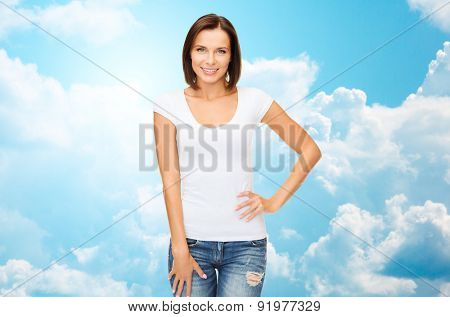 people, advertisement and clothing concept - happy woman in blank white t-shirt over blue sky with white clouds background