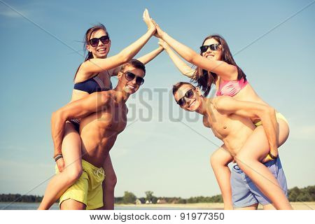 friendship, sea, gesture, holidays and people concept - group of smiling friends wearing swimwear having fun and making high five on beach