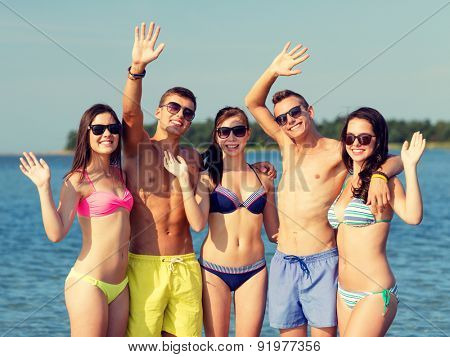 friendship, sea, holidays, gesture and people concept - group of smiling friends wearing swimwear and sunglasses waving hands on beach
