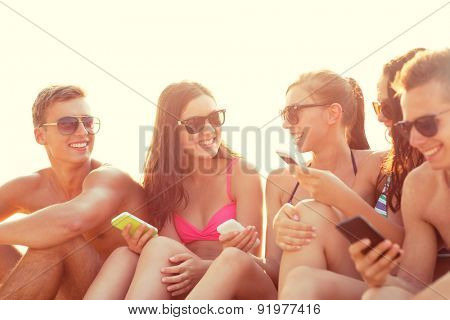 friendship, leisure, summer, technology and people concept - group of smiling friends with smartphones on beach