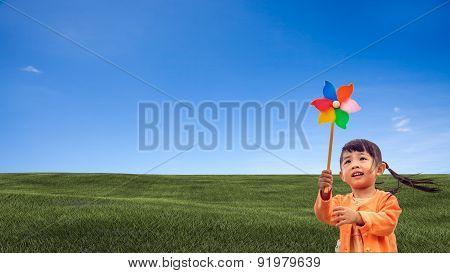 Closeup Of Little Girl Blowing Wind Wheel