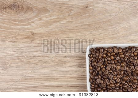 coffee beans in a porcelain bowl on wooden background