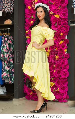 the girl in a yellow dress in a clothing store