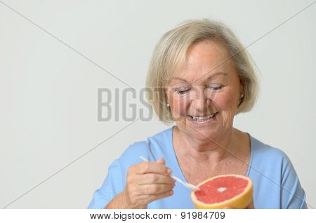 Happy Healthy Senior Lady With A Red Grapefruit