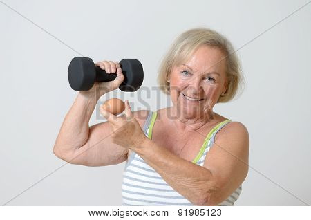 Senior Lady Holding A Dumbbell And Egg