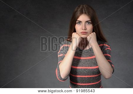 Girl Shows Concentration Against A Dark Background
