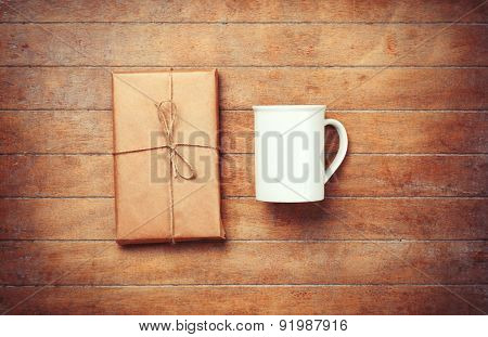 White Cup And Package On Wooden Table.