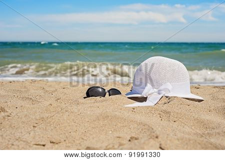 Wicker white hat and sun glasses on the beach