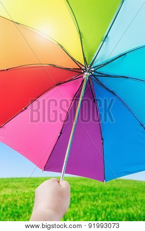 Rainbow Umbrella In Woman Hands On Nature