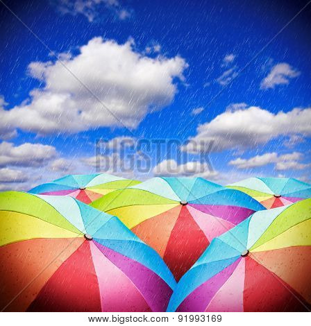 Rainbow Umbrellas Against The Sky With Rain