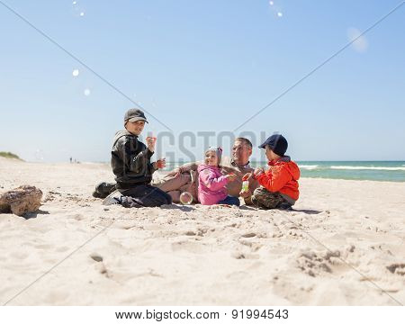 family on beach,  father of many children,  kids blowing bubbles
