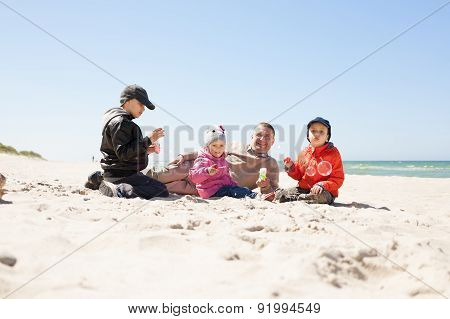 beach, family lying on sand and play, father of many children, kids blowing bubbles