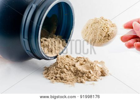The hand raise a spoon measure Whey protein chocolate powder for fitness and bodybuilding gaining mu