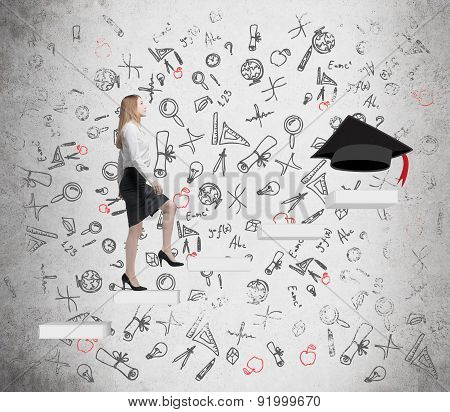 Young Lady Is Going Up To Graduate University. Graduation Hat As A Prize At The End Of The Education