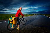 image of bicycle gear  - Woman riding loaded bicycle on the wet asphalt road with clouds on the background - JPG