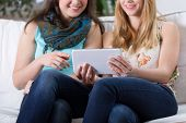 picture of two women taking cell phone  - Two teenage girls looking at a tablet - JPG