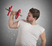 foto of fatigue  - Fatigued fat man sweats while lifting weights - JPG