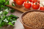 picture of ceramic bowl  - Composition with ceramic bowl dry buckwheat tomatoes and parsley in the background - JPG