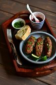 stock photo of cilantro  - kebabs with berry sauce and cilantro in a vintage tray on a dark wooden surface - JPG