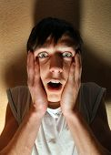 stock photo of shock awe  - Scared Young Man in the Dark Room by the Wall - JPG