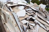 stock photo of eviction  - in a waste container stacks sheets of plasterboard for their disposal - JPG