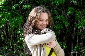 stock photo of ferrets  - Joyful girl with ferret in the hands on a walk in a sunny day - JPG