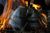 foto of boil  - Boiling water in a kettle by fire in a camping - JPG