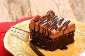 pic of chocolate fudge  - Chocolate sheet cake covered with chocolate icing and chocolate syrup on a plate with a fork - JPG