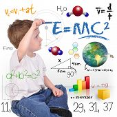 stock photo of math  - A young boy child is writing out math and science equations and formulas - JPG