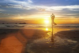 picture of sea life  - Silhouette of woman standing at yoga pose on the beach during amazing sunset - JPG