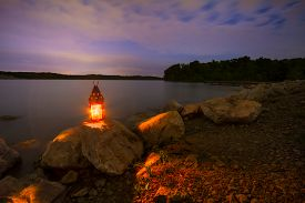 pic of dock a lake  - Blue Springs Lake located outside of Kansas City Missouri at night with a lantern glowing light onto the rocky shoreline - JPG