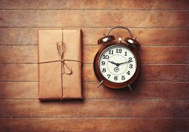 foto of packages  - Retro alarm clock and package on wooden table - JPG