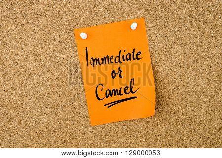 Immediate Or Cancel Written On Orange Paper Note