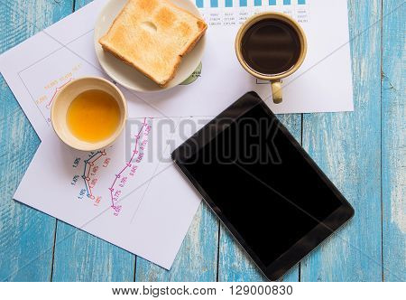Black display Tablet Toast Honey Coffee cup Graph data analysis placed on blue wooden floor.Image Graph and Toast on tablet display.