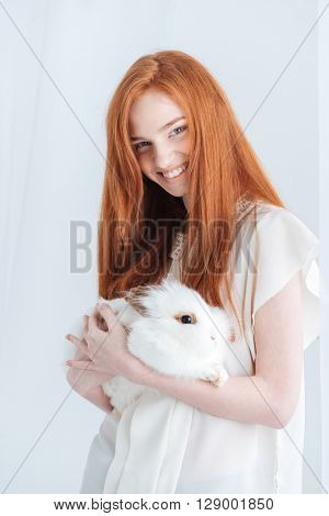 Smiling redhead woman holding rabbit isolated on a white background