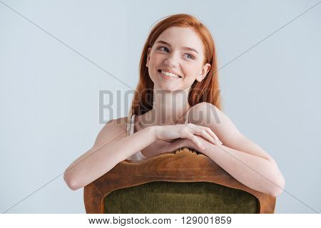 Smiling redhead woman sitting on the chair and looking away isolated on a white background